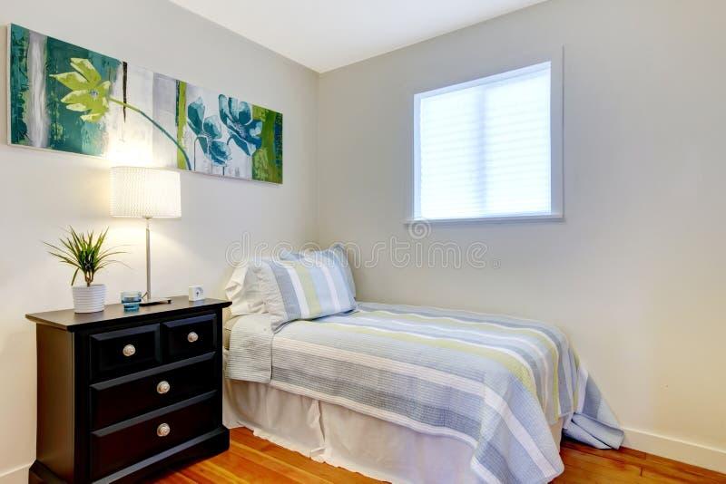 Einfaches Schlafzimmer mit schwarzem nightstand und Anstrich. stockbild