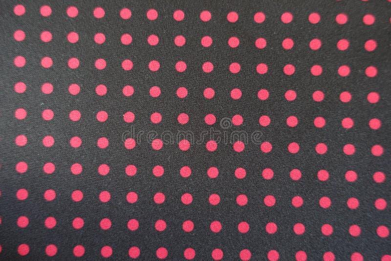 Einfaches schwarzes Gewebe mit rotem Tupfendruck lizenzfreie stockfotos