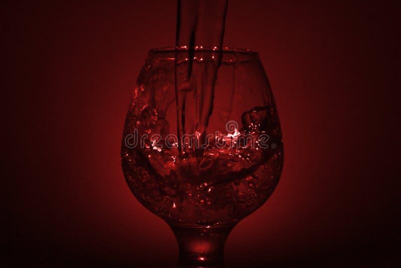 Einfaches Stilllebenfoto Whiskyglas-, Wasserstrahl- und schwachemrotes L stockfotografie