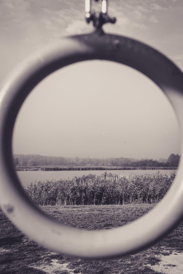 Einfarbige Ansicht durch Kreis auf dem See und den Schilfen stockbild