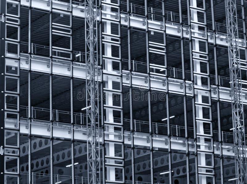 Einfarbige blaue abgetönte Ansicht einer großen errichtenden Entwicklung im Bau mit Stahlgerüst und Trägern lizenzfreies stockfoto
