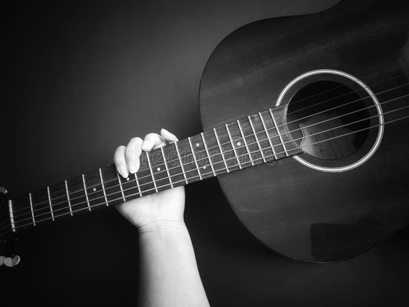 Einfarbige Hand, welche die Akustikgitarre hält stockbild