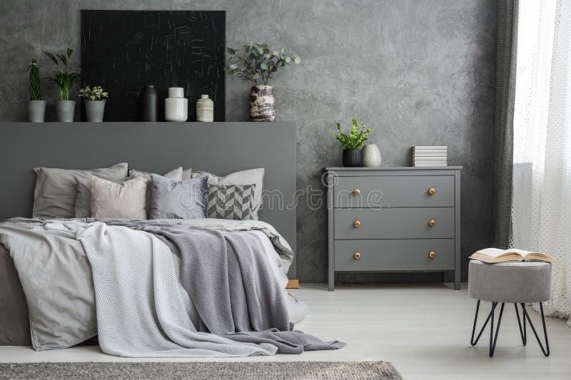 Einfarbiger grauer Schlafzimmerinnenraum mit einem großen Bett mit Würfen a stockbild