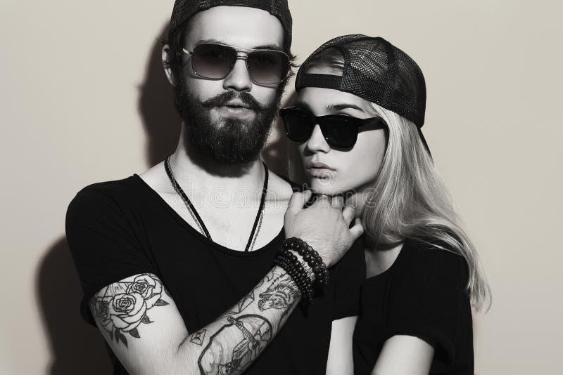Einfarbiges Porträt von schönen Paaren zusammen Tätowierungs-Hippie Junge und gir stockbild