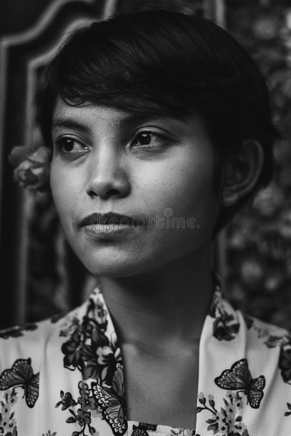 Einfarbiges Retro- Schwarzweiss-Portr?t einer sch?nen kurzes Haar asiatischen Balinesefrau, die Blumenstoffweinleseart tr?gt und stockfoto
