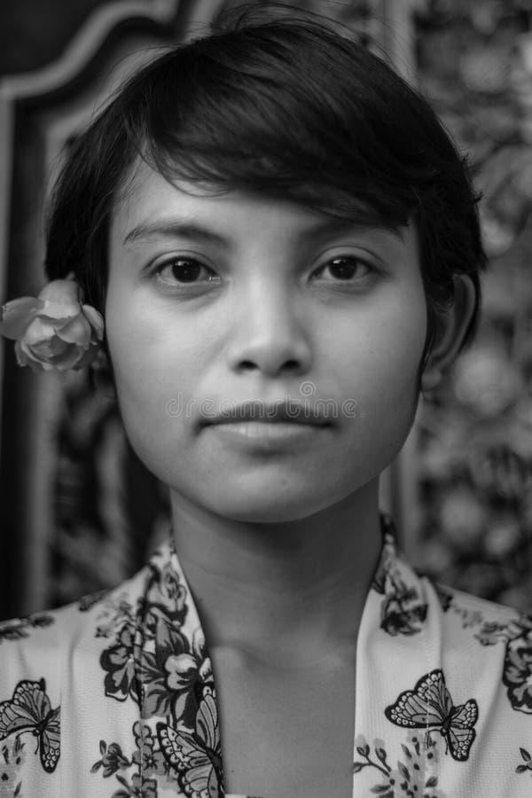Einfarbiges Retro- Schwarzweiss-Portr?t einer sch?nen kurzes Haar asiatischen Balinesefrau, die Blumenstoffweinleseart tr?gt und stockbild