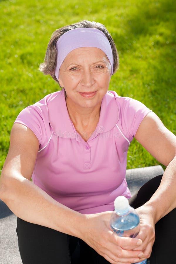 Einfluss-Flaschenwasser der älteren sportiven Frau glückliches stockfotos