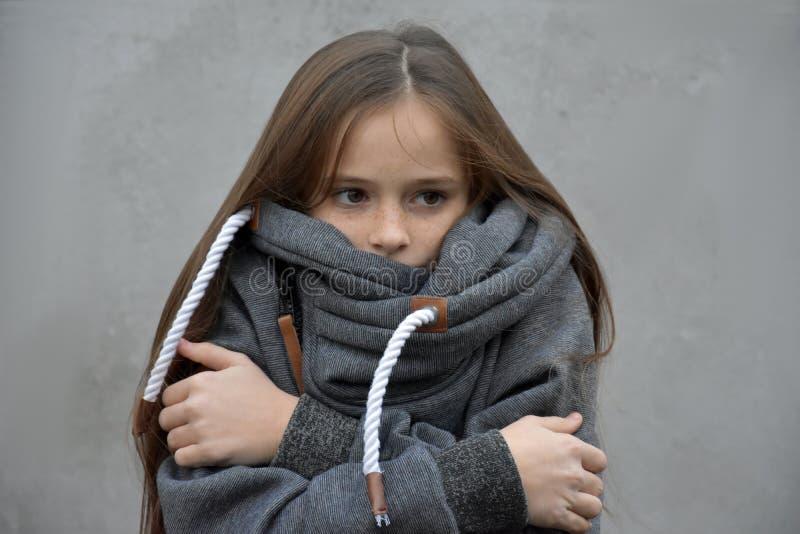 Einfrierendes Mädchen schmiegt sich in ihrer woolen Strickjacke an stockfotografie