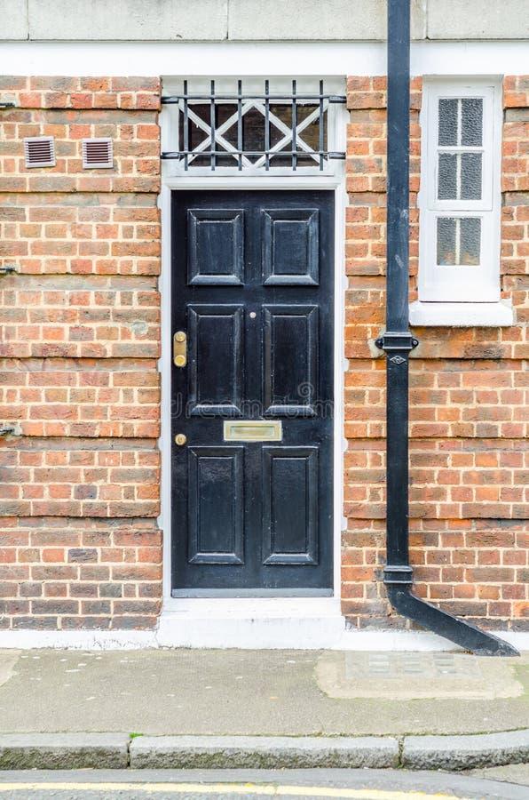 Eingang von der Außenseite zu einem Backsteinbau, eine stilvolle schwarze Tür, stockfotografie