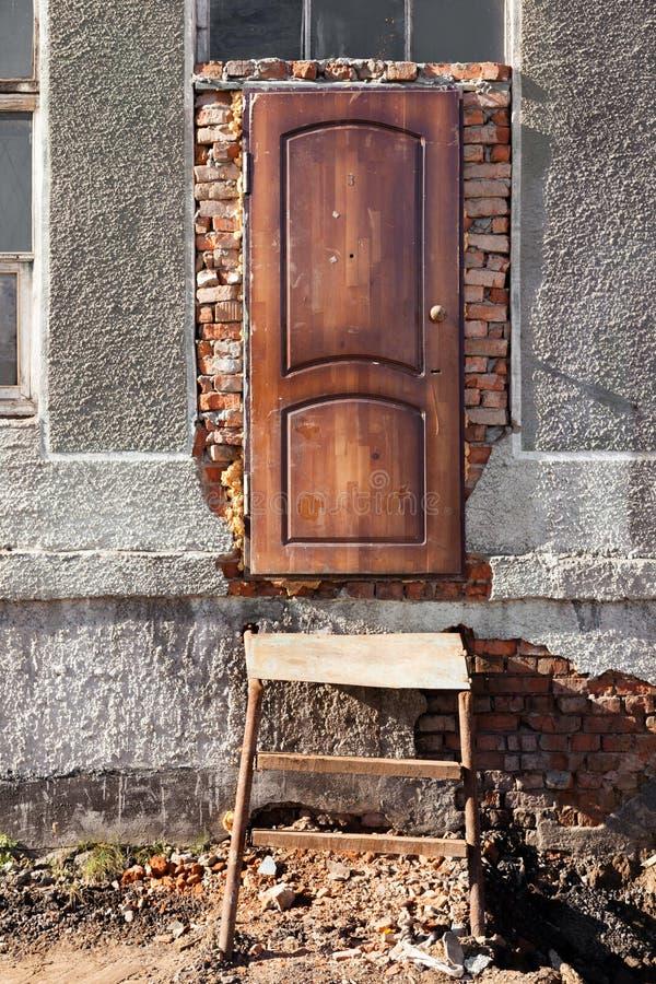 Eingang zu zerstörtem Gebäude, Holztür, Metalltreppenhaus, wi lizenzfreies stockfoto