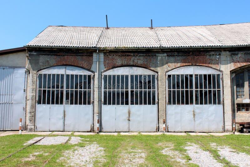 Eingang zur großen alten Bahnstationsreparaturwerkstatt mit den überwucherten Bahngleisen, die zu Haustüren führen lizenzfreie stockbilder