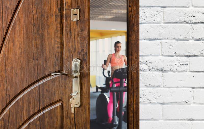 Eingang zur Turnhalle im Fitness-Club, geöffnete Tür mit Frau auf elliptischem Trainer stockbilder