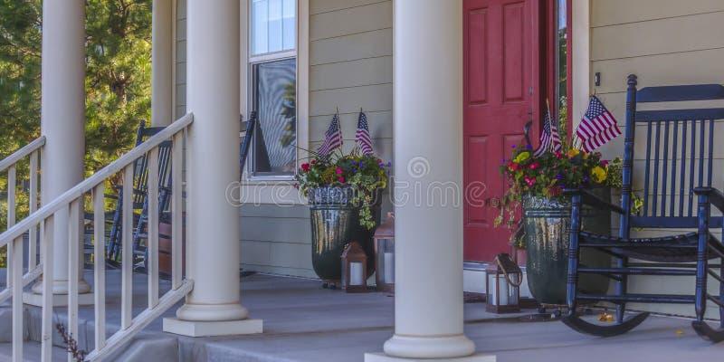 Eingangsterrasse mit roter Tür und Schaukelstuhl der Treppe stockfoto