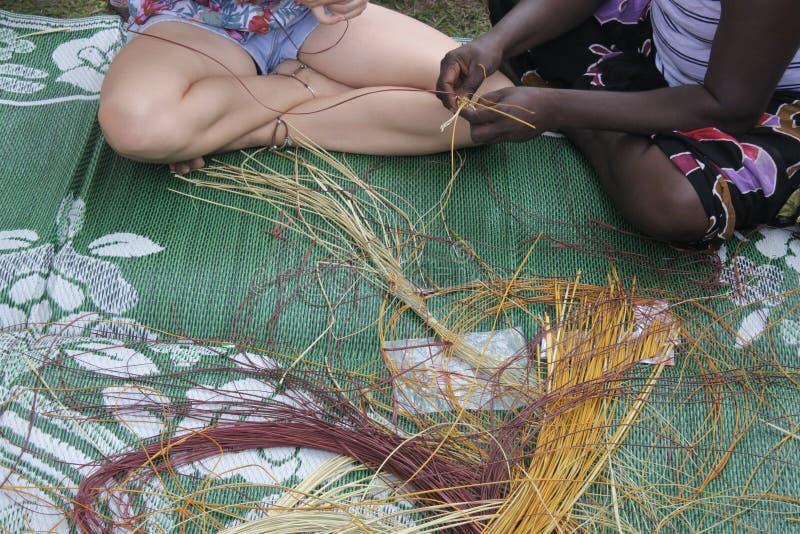 Eingeborene Frau der einheimischen Australier, die ein touristisches eingeborenes Korbflechten unterrichtet stockbild