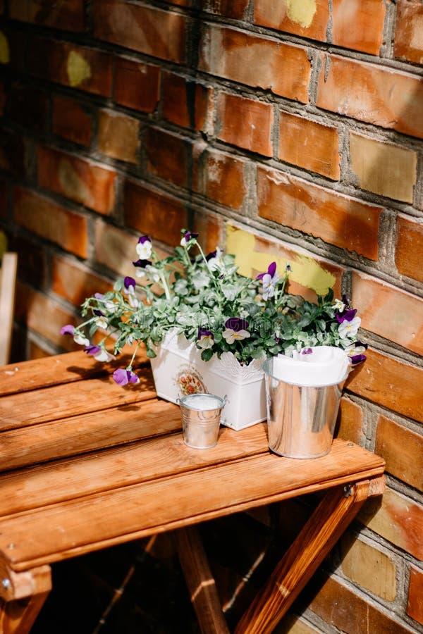 Eingemachte Frühlingsblumen auf Holztisch Gartenarbeitszene der Weinlese mit Stiefmütterchenblumen in der alten Emailschüssel lizenzfreie stockfotos