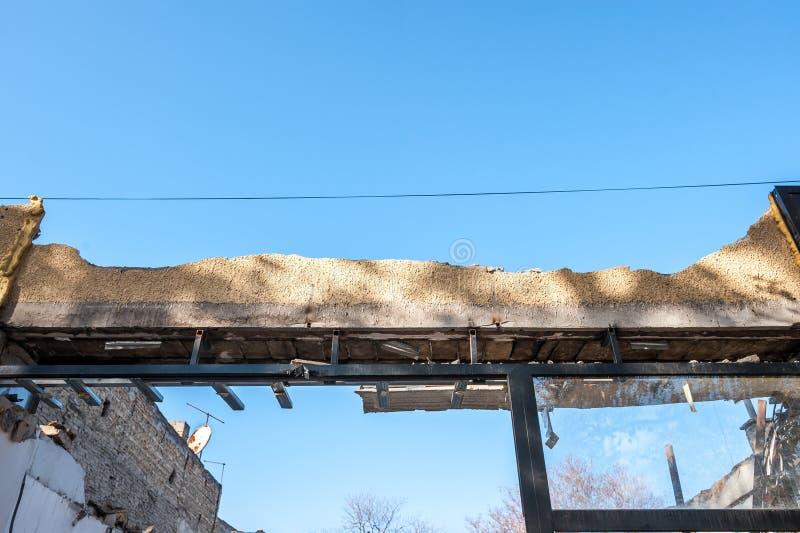 Eingestürztes Dach nach Nachwirkungserdbeben oder Hurrikan auf dem alten ruinierten inländischen Haus mit zerbrochenen Fenstersch stockfotografie