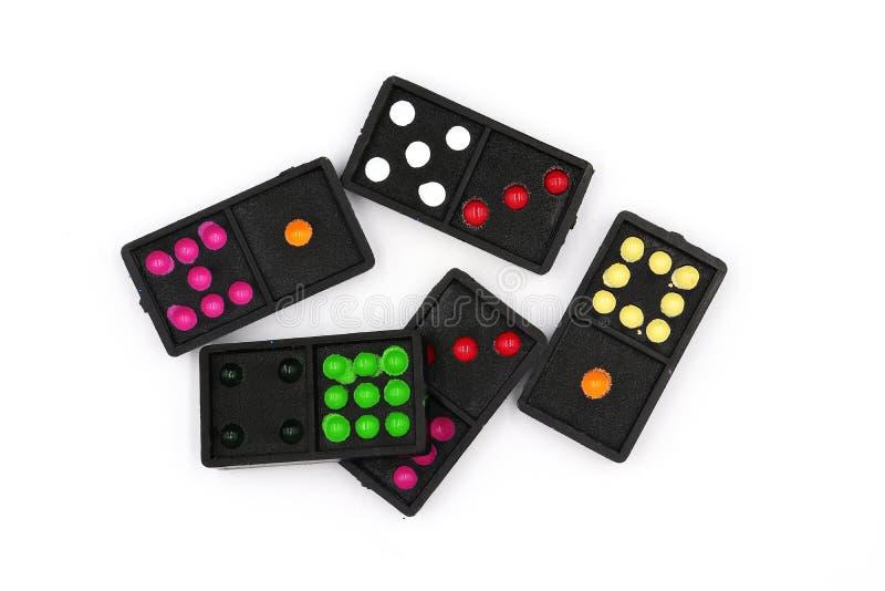 An eingestellt von den Dominos, schließen Dominolüge, oben alte schwarze Farbdominos mit den bunten Punktstücken, die auf weißem  lizenzfreie stockfotos