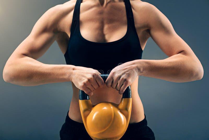 Eingestuft herauf Ansicht über das junge muskulöse Mädchen, das schweres kettlebell hält stockbilder
