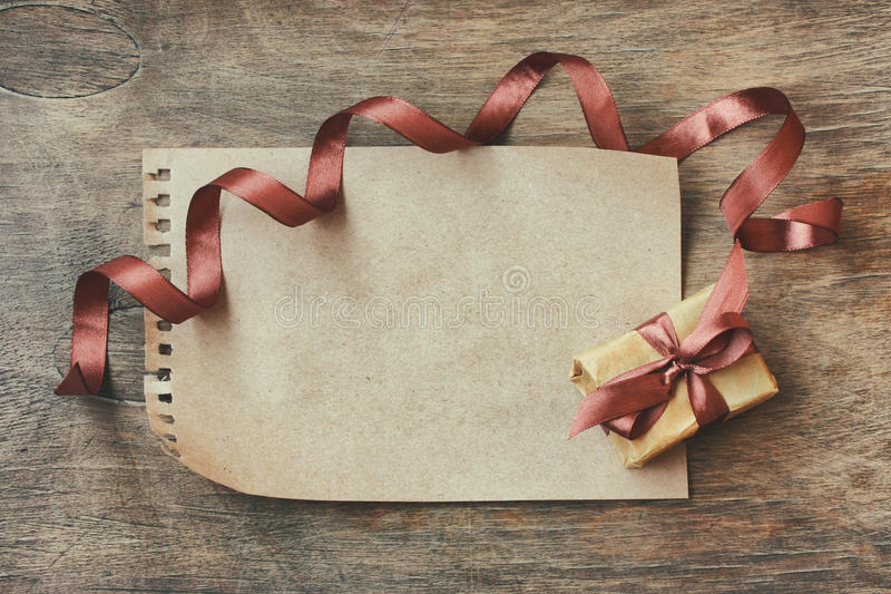 Eingewickelte Geschenkbox des Feiertags Hintergrund, braunes Seidenband stockbild