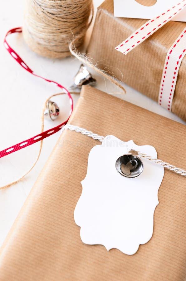 Eingewickelte Geschenke verziert mit silbernen Glocken und Geschenktags stockbild