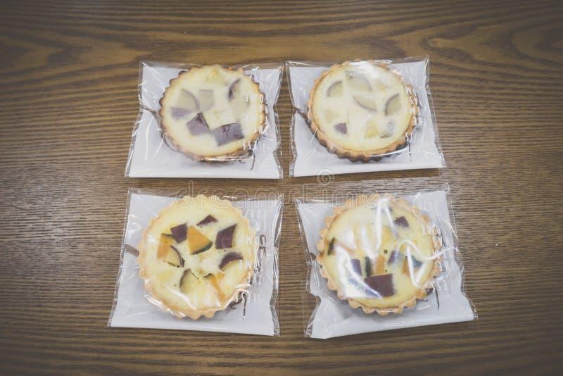 Eingewickelte süße Kürbis- und Süßkartoffeltorten auf Holztisch lizenzfreie stockbilder