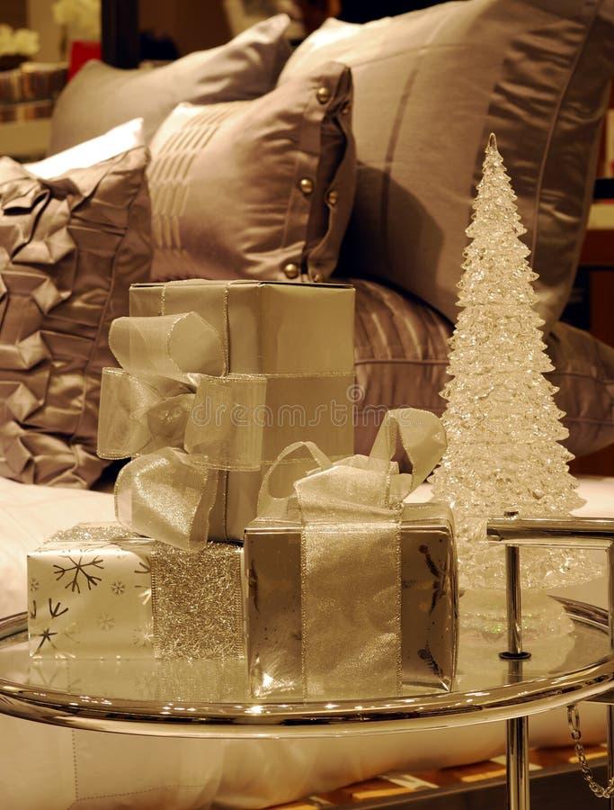 Eingewickelte Weihnachtsgeschenke auf einer Glastabelle stockfotos