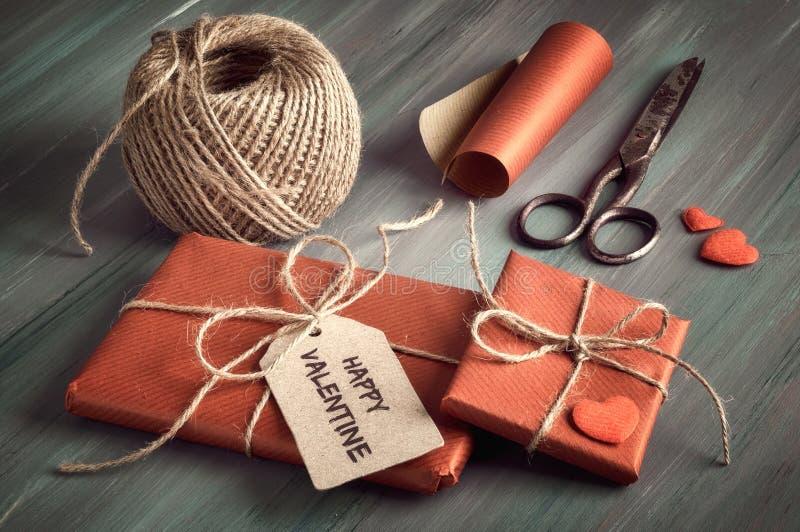 Eingewickeltes Geschenk mit Tag ` glücklichem Valentinsgruß `, brauner Schnur, Packpapier, Scheren und dekorativen Herzen stockfotos