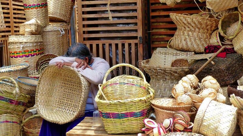 Einheimischer Handwerksmarkt des Frauenhändlers t in Cuenca unter gesponnenen Taschen und Körben, Ecuador lizenzfreie stockfotografie