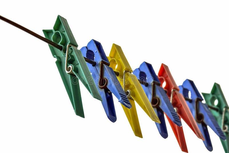 Einige alte farbige Leinenwäscheklammern auf dem Metalldraht lokalisiert auf weißer Hintergrundnahaufnahme stockfoto