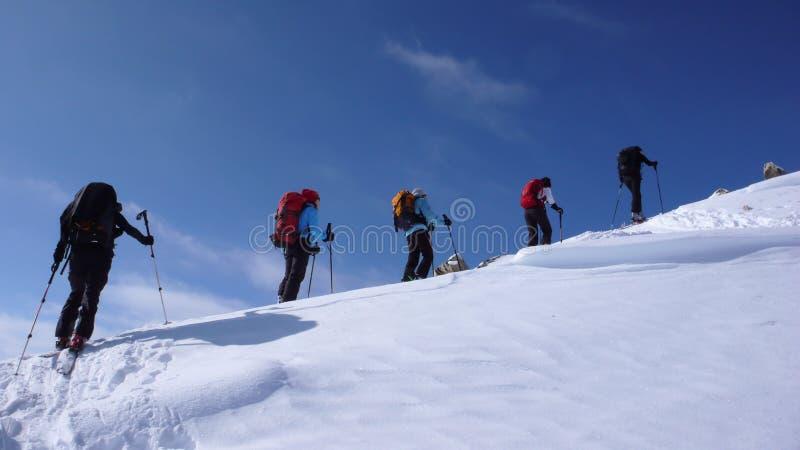 Einige backcountry Skifahrer zu einer Fernbergspitze in der Schweiz an einem schönen Wintertag wandern und klettern lizenzfreie stockfotos