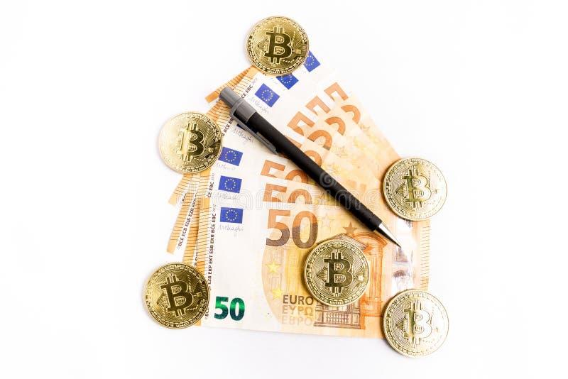Einige bitcoin Goldmünzen nahe bei einigen Eurorechnungen und einem Stift stockbilder