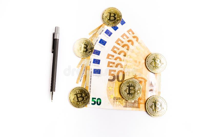 Einige bitcoin Goldm?nzen nahe bei einigen Eurorechnungen und einem Stift stockfoto