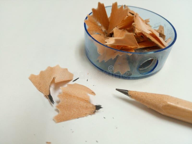 Einige Bleistiftschnitzel in einem Bleistiftspitzer und einige Bleistiftschnitzel mit einem Bleistift sind auf weißem Hintergrund lizenzfreies stockbild