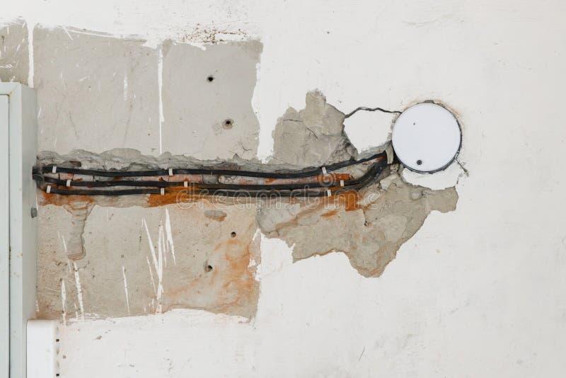 Einige elektrische Kabel werden in der schädigenden Wand verlegt lizenzfreie stockfotos