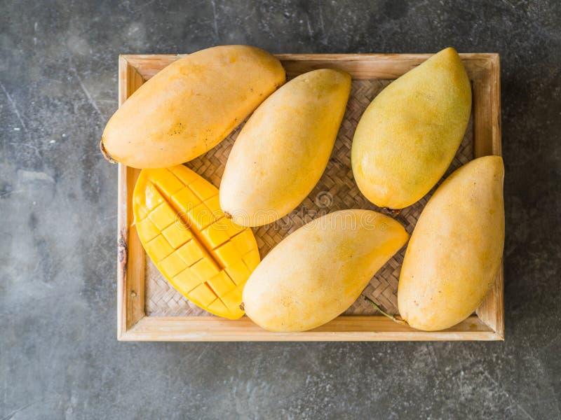 Einige frische süße gelbe thailändische Mangos auf einem hölzernen Behälter auf einem grauen Hintergrund stockfotografie