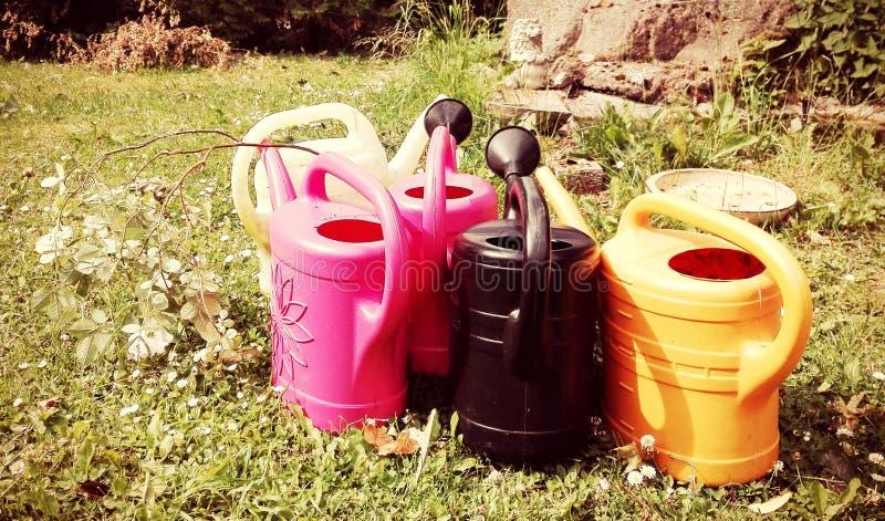 Einige Gießkannen in den verschiedenen Farben steht in einem grünen Garten ein sonnigen Sommertag lizenzfreies stockfoto