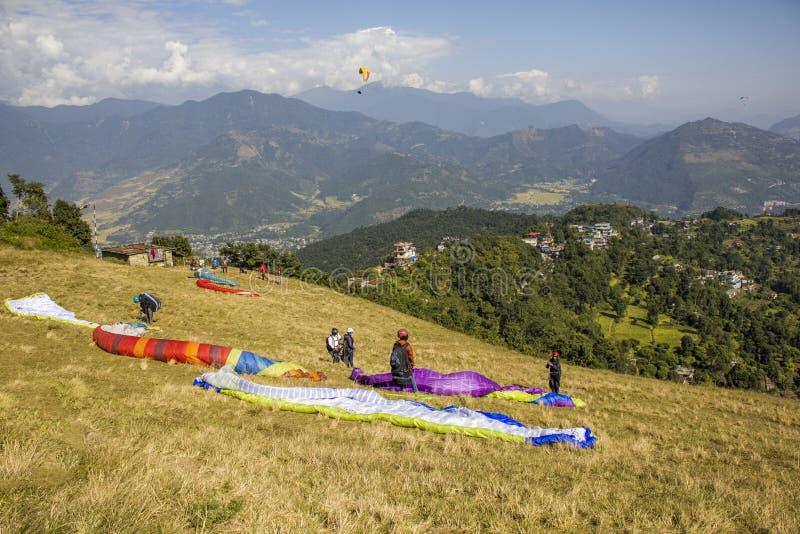 Einige Gleitschirme auf der Steigung bereiten vor sich, sich vor dem hintergrund eines grünen Berges zu entfernen stockfotos