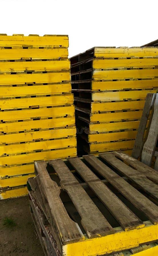 Einige große Stapel der gelben hölzernen Paletten stockfotografie