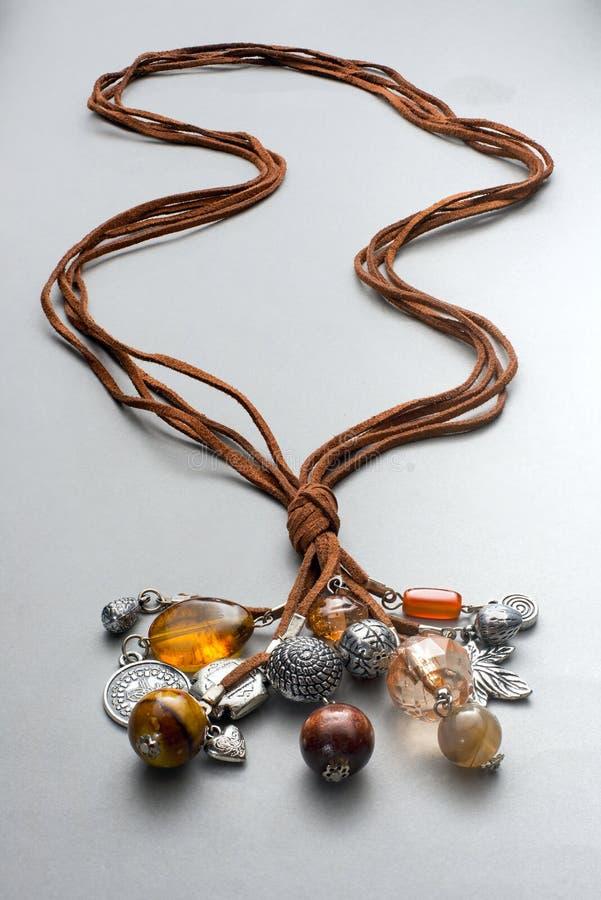 Einige Halsketten zusammen geknotet auf Grau lizenzfreies stockbild