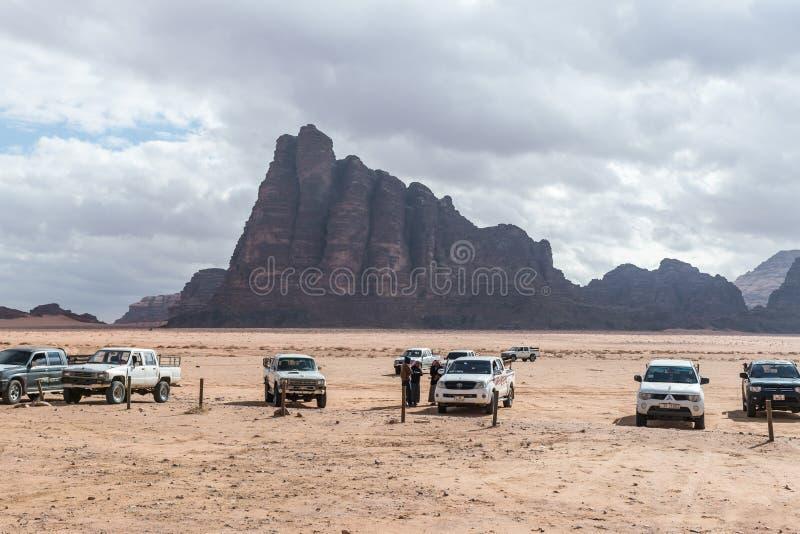 Einige Jeeps und ihre Fahrer warten auf Touristen nahe Wadi Rum Visitor Center am Eingang zu Wadi Rum-Wüste nahe Aqab lizenzfreies stockbild