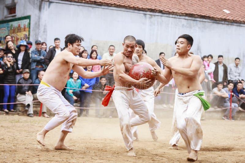 Einige junge Männer spielen mit hölzernem Ball im neuen Mondjahr des Festivals in Hanoi, Vietnam am 27. Januar 2016 stockfotografie