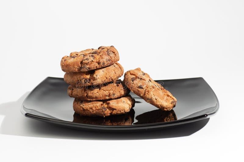 Einige köstliche Schokoladenplätzchen auf einem Schwarzblech lokalisiert auf weißem Hintergrund stockbild