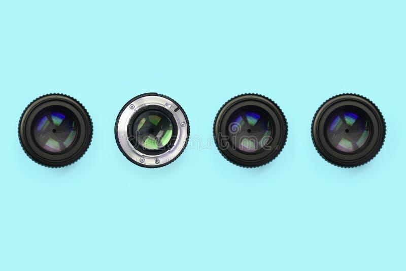 Einige Kameraobjektive mit einer geschlossenen Öffnungslüge auf Beschaffenheitshintergrund des blauen Pastellpapiers der Mode Far stockbilder