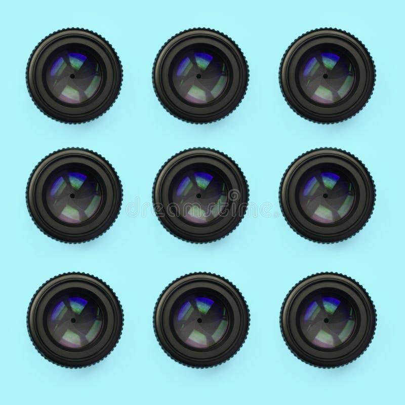 Einige Kameraobjektive mit einer geschlossenen Öffnungslüge auf Beschaffenheitshintergrund des blauen Pastellpapiers der Mode Far lizenzfreies stockfoto