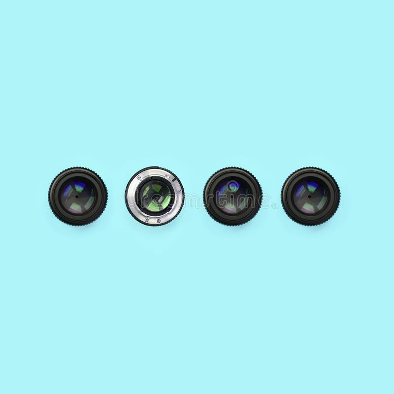 Einige Kameraobjektive mit einer geschlossenen Öffnungslüge auf Beschaffenheitshintergrund des blauen Pastellpapiers der Mode Far lizenzfreie stockfotos