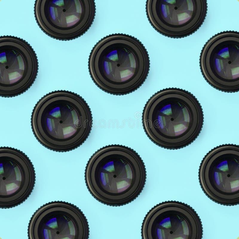 Einige Kameraobjektive mit einer geschlossenen Öffnungslüge auf Beschaffenheitshintergrund des blauen Pastellpapiers der Mode Far lizenzfreie stockbilder