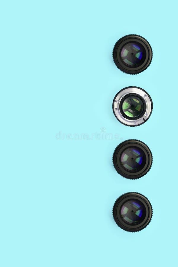 Einige Kameraobjektive mit einer geschlossenen Öffnungslüge auf Beschaffenheitshintergrund des blauen Pastellpapiers der Mode Far lizenzfreie stockfotografie