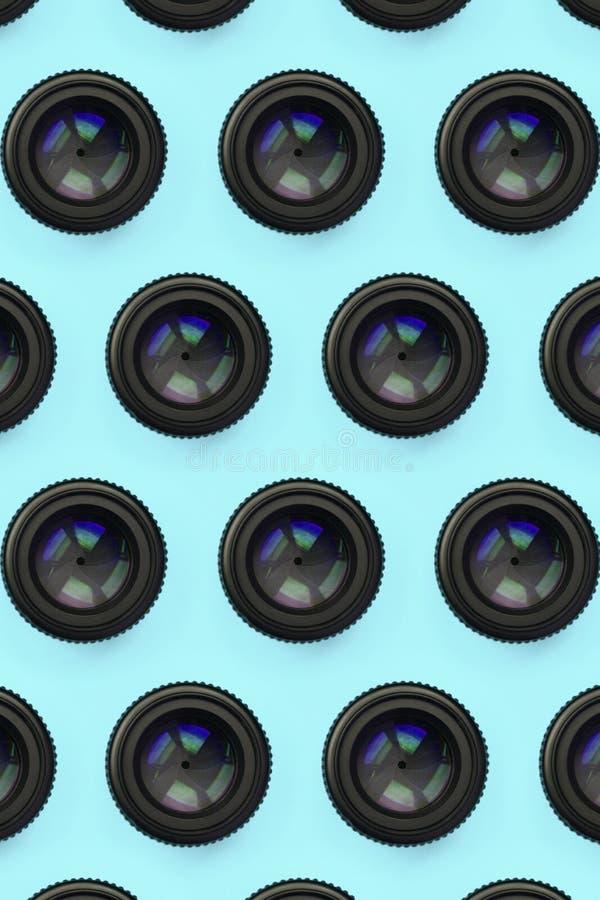 Einige Kameraobjektive mit einer geschlossenen Öffnungslüge auf Beschaffenheitshintergrund des blauen Pastellpapiers der Mode Far stockfotografie