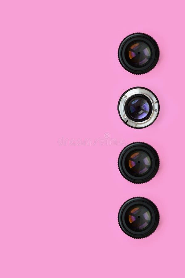 Einige Kameraobjektive mit einer geschlossenen Öffnungslüge auf Beschaffenheitshintergrund des rosa Pastellpapiers der Mode Farbi stockfoto