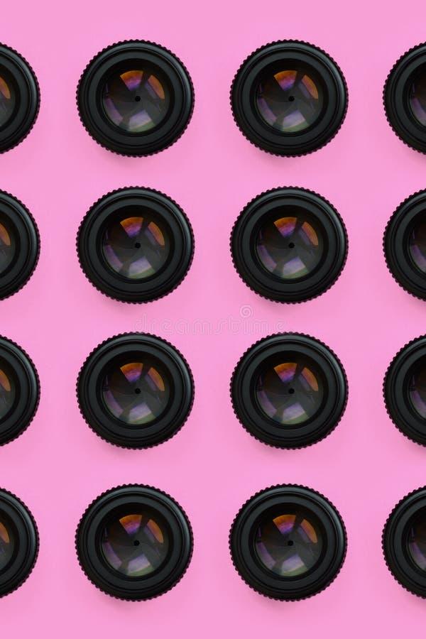 Einige Kameraobjektive mit einer geschlossenen Öffnungslüge auf Beschaffenheitshintergrund des rosa Pastellpapiers der Mode Farbi stockfotos